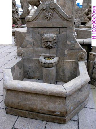 Man face motif stone sculpture as wall fountain with basin and pillar for garden decoration