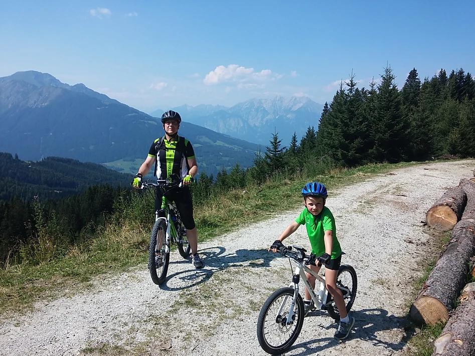 Kind und Erwachsener mit den E-Bikes vor einer wunderschönen Aplenaussicht