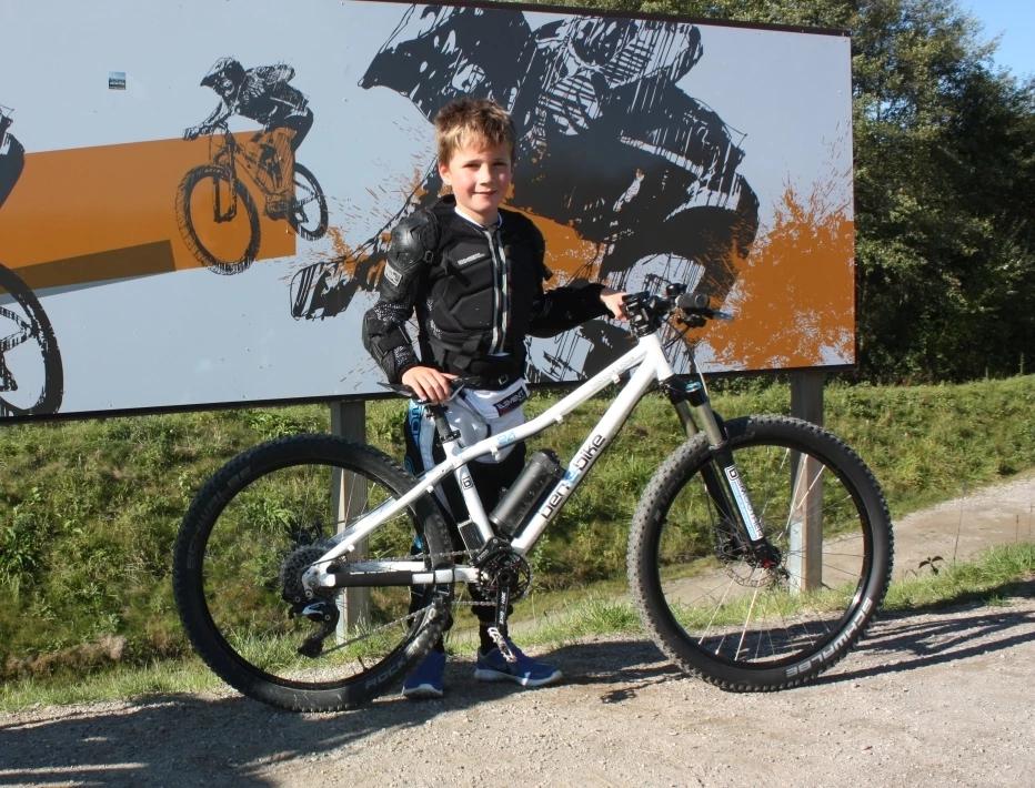 Ben mit dem E-Bike vor einem Schild