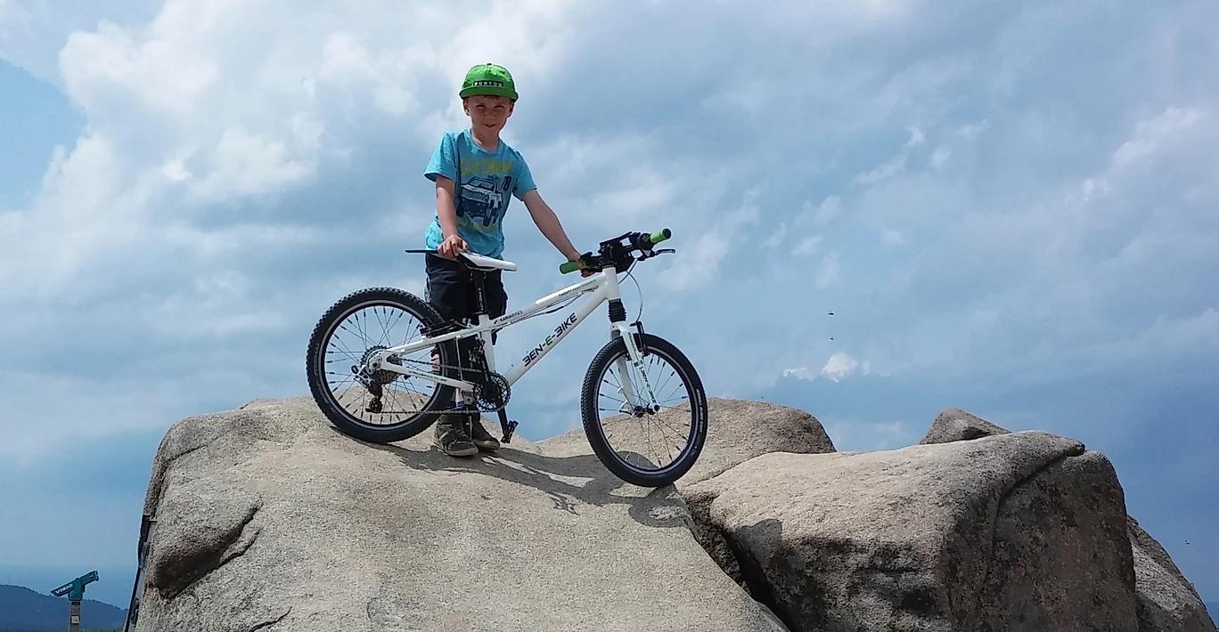Kind mit dem E-Bikes oben auf einen großen Steinbrocken