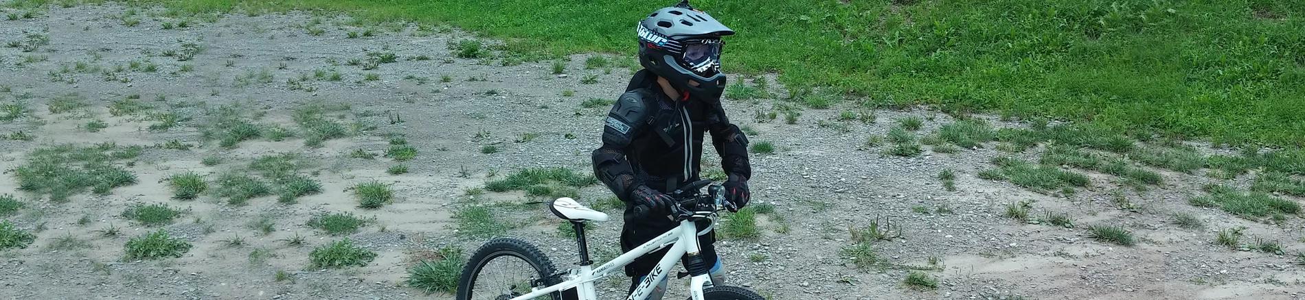Kind auf einem E-Bike mit Sicherheitsausrüstung im Freien