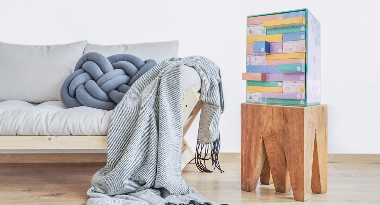 Wunderkinder Schwangerschaftskalender auf einem Holztisch mit Sofa in der linken ecke