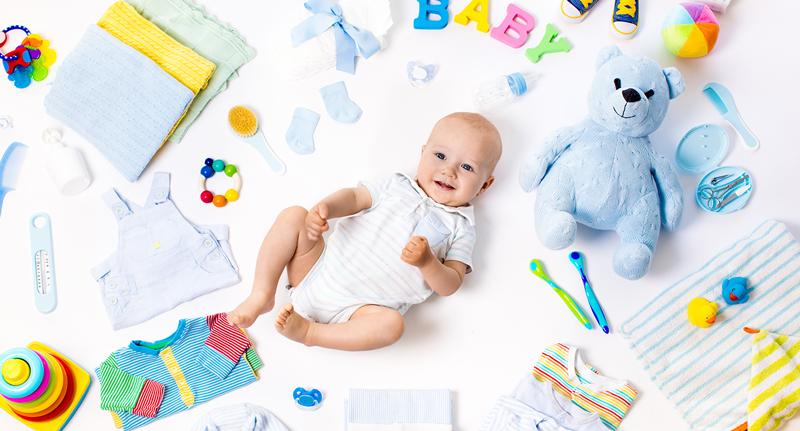Babyausstattung - Baby in der Mitte und ganz viel Spielzeug und Kleidung um ihn herum