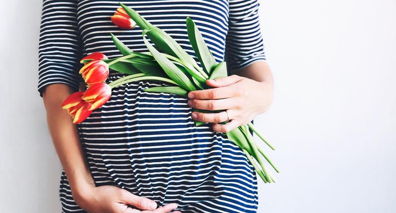 Schwangere Frau mit gelb-roten Tulpen in der Hand