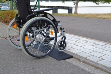 Bordstein mit Rollstuhl überfahren