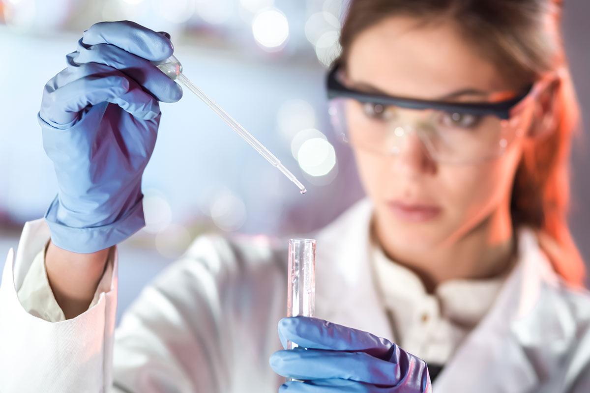 Eine Laborantin füllt Aqua bidest mit einer Pipette in ein Reagenzglas