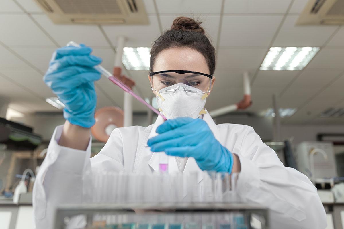 Eine Laborantin füllt bei der Forschung Aqua dest mit einer Pipette in ein Reagenzglas