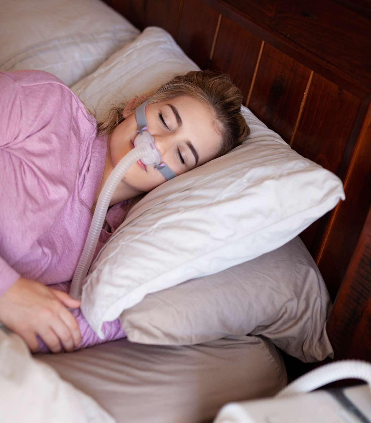 Frau schläft ruhig dank perfekt sitzender CPAP-Maske