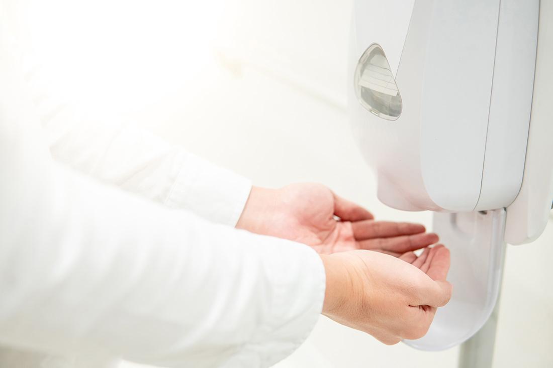 Ein Arzt desinfiziert sich die Hände an einem Desinfektionsmittelspender