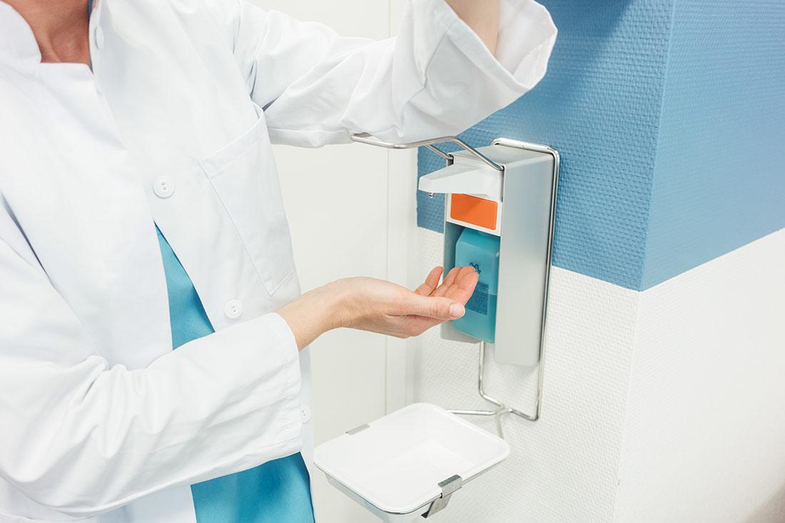 Eine Ärztin desinfiziert sich die Hände an einem Desinfektionsspender
