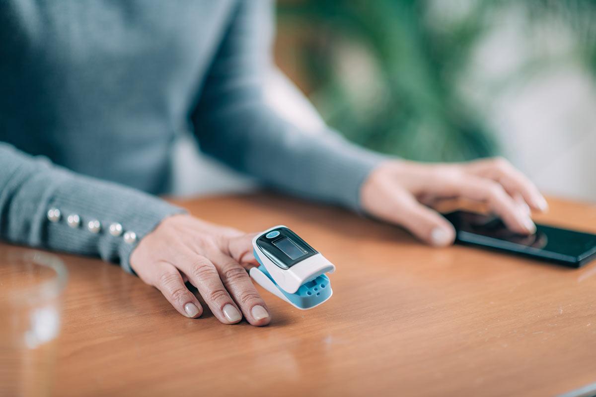 Die Hand einer Seniorin ist mit einem Fingerpulsoximeter versehen.