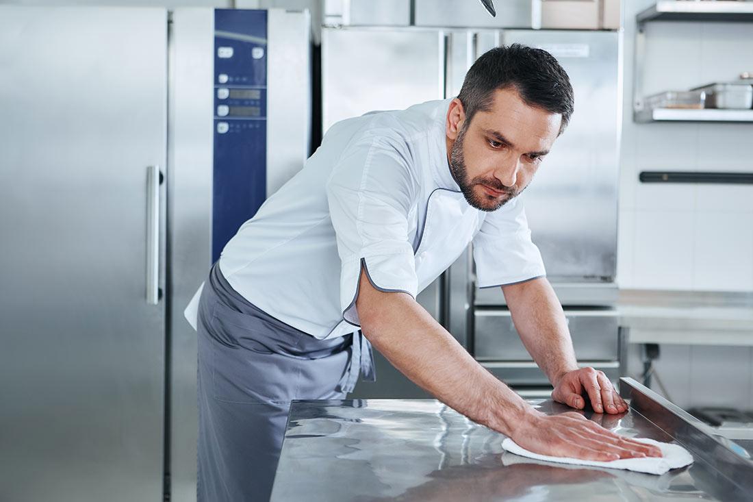 Koch reinigt Arbeitsfläche mit Flächendesinfektionsmittel aus dem Sortiment