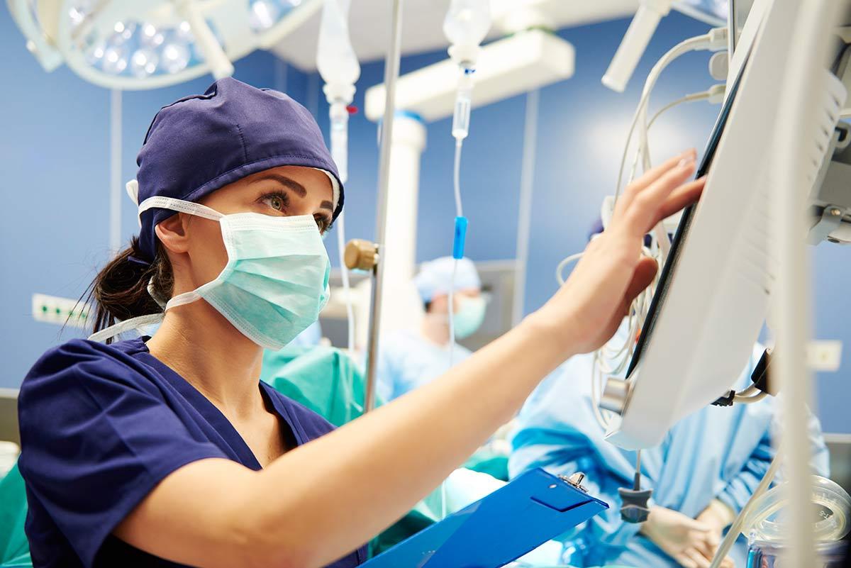 OP-Schwester arbeitet im Krankenhaus mit Handpulsoximeter und Monitoren