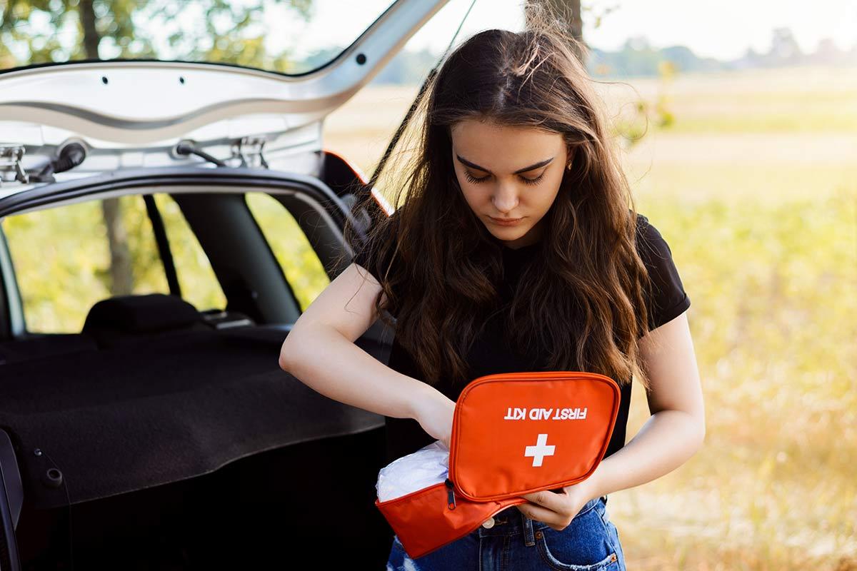 Junge Frau steht neben dem Kofferraum und sucht Material aus der KFZ-Verbandtasche aus