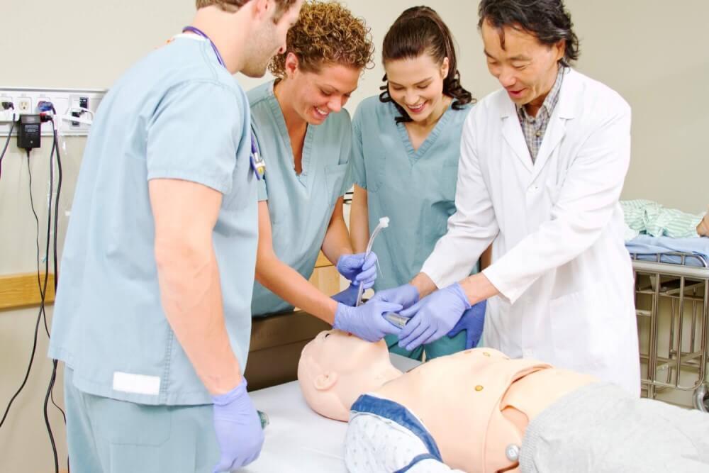 :Arzt erklärt Studenten die Intubation an einer medizinischen Übungspuppe