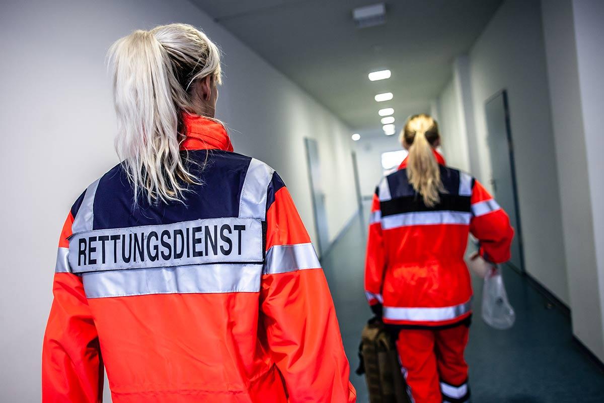 Zwei Sanitäterinnen in einem Flur, mit einem Notfallrucksack gefüllt sind sie schnell bereit zu helfen