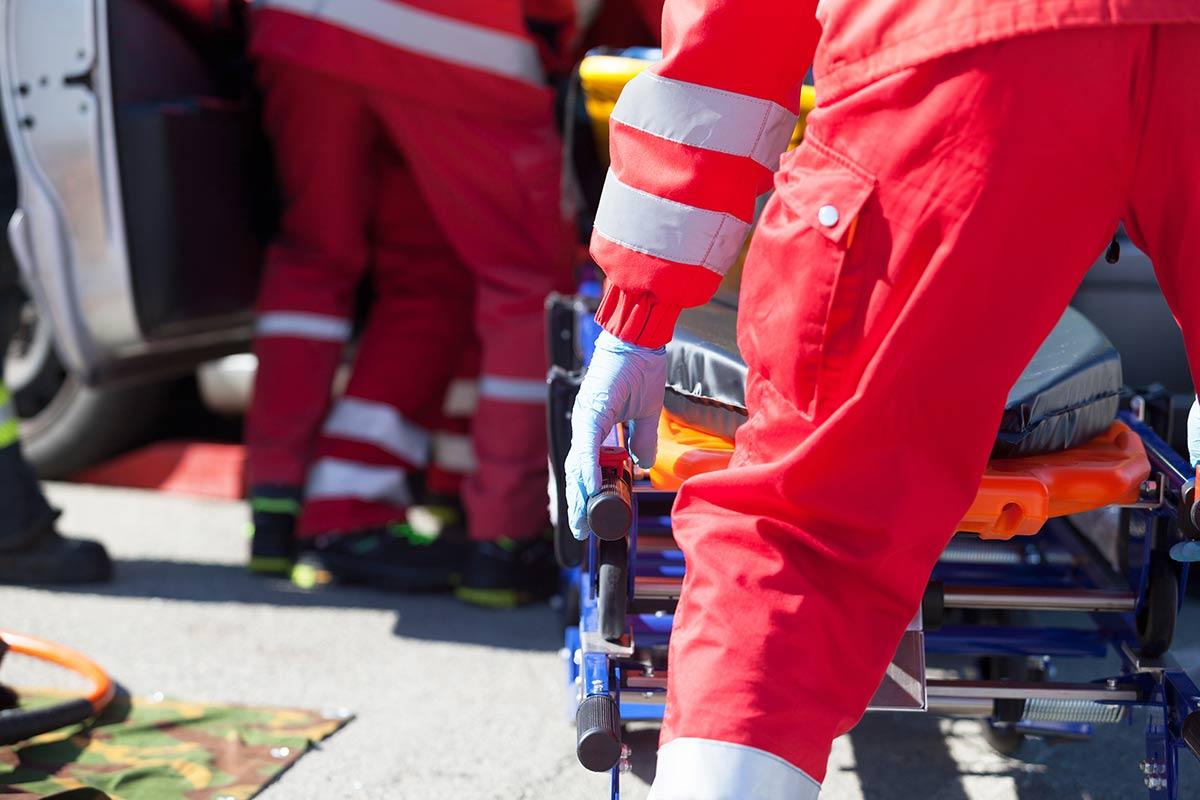 Notfallkräfte in leuchtendem Rot im Einsatz – eine Notfalltasche gefüllt nach Norm in Signalfarben bleibt sichtbar