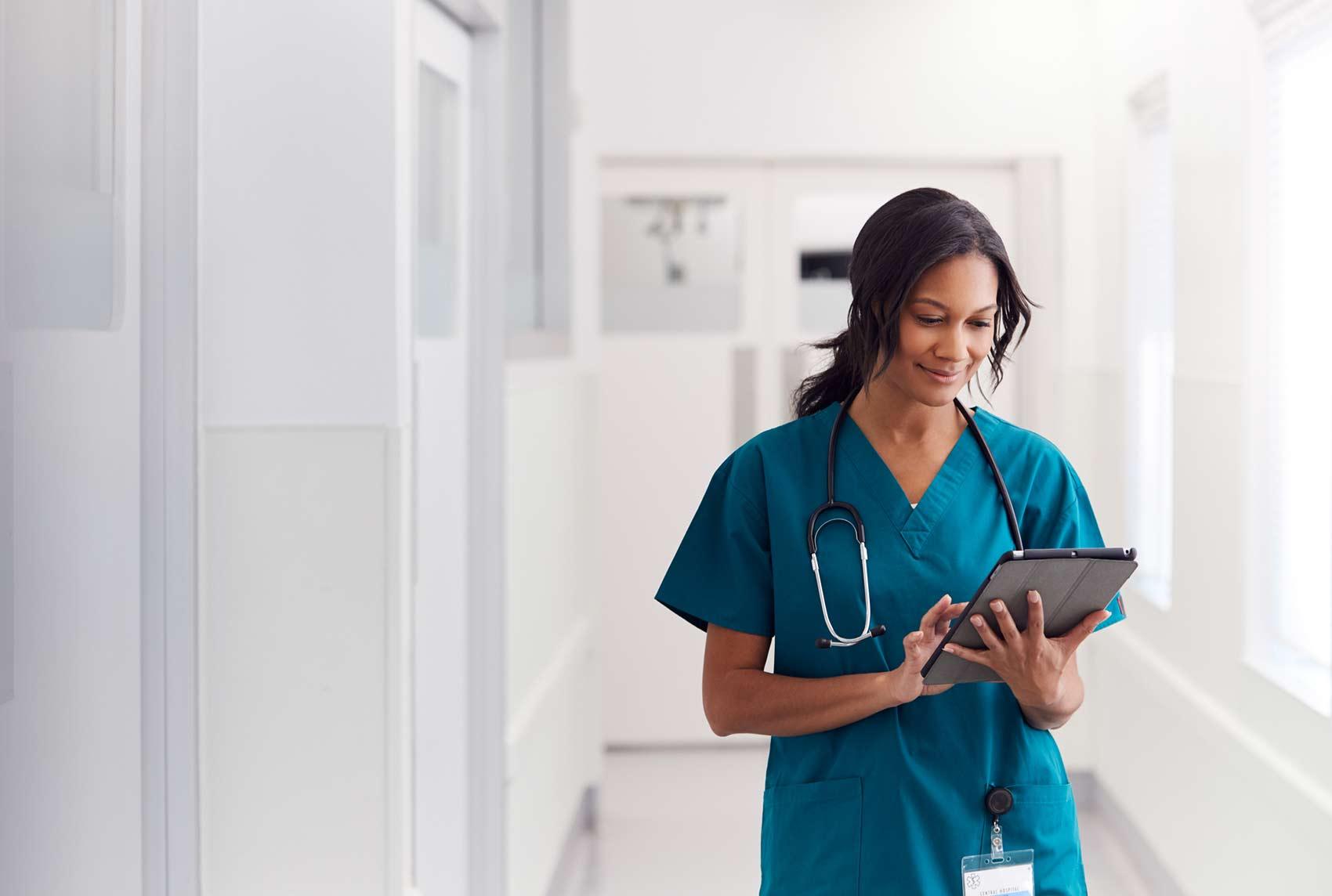 Ärztin mit Tablet in der Hand trägt OP-Bekleidung