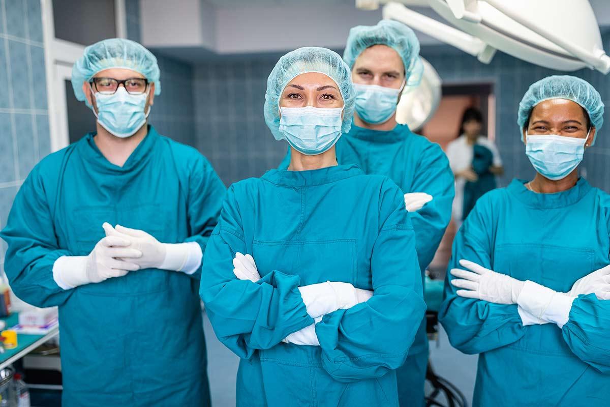 Ärzteteam im Operationssaal trägt OP-Handschuhe