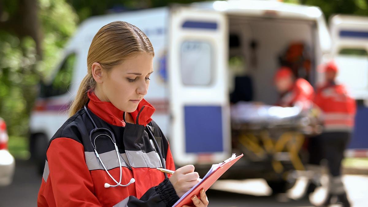 Notfallsanitäterin notiert vor Ambulanz mit Stift auf Klemmbrett Informationen – Organisationsmittel erleichtern solche Vorgänge