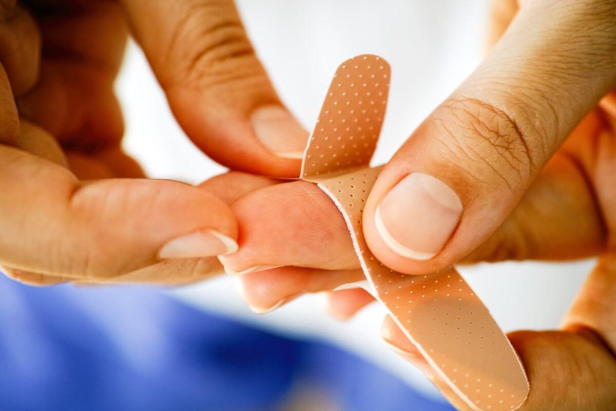 Nahaufnahme einer Frau, die sich ein Pflaster am Finger aufklebt