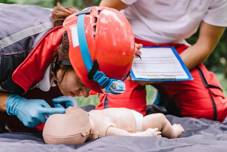 Feuerwehrfrau trainiert mit Rettungspuppe eines Babys
