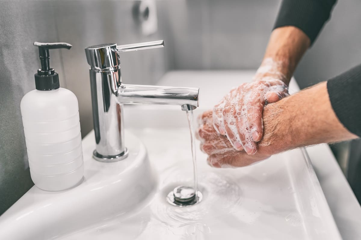 Eine Person schäumt sich die Hände ein mit Seife aus dem Schaumseifenspender