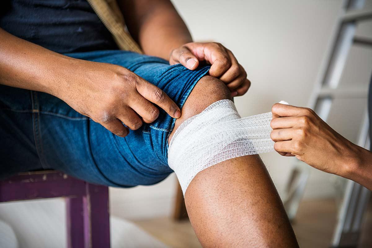 Frau verbindet das Knie eines Mannes mit Bandage aus einem Verbandkasten Nachfüllset