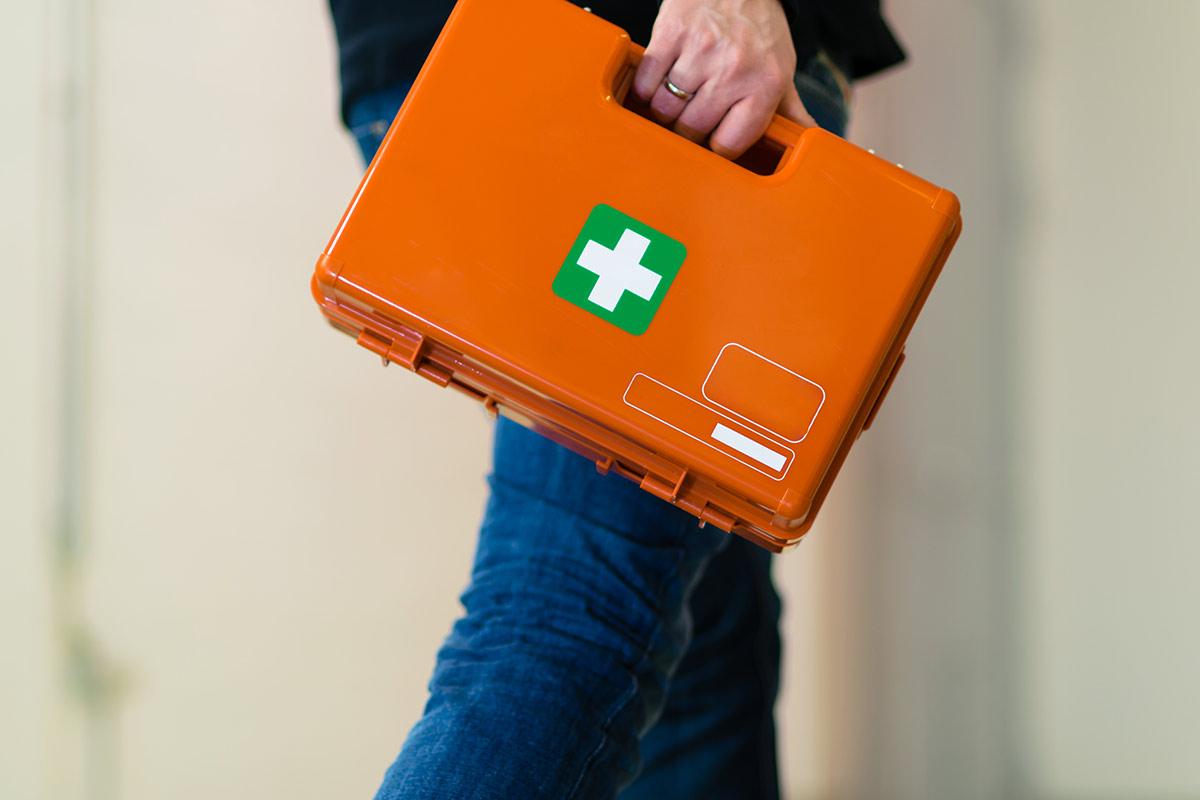 Mann trägt einen Verbandskasten durch einen Flur einer Firma zum Unfallort