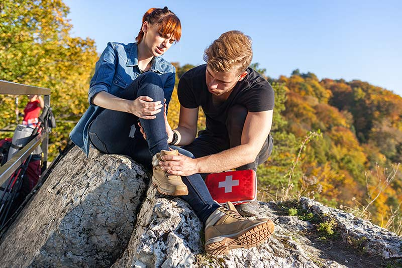 Mann mit Verbandtasche kümmert sich um verletzte Frau in den Berge