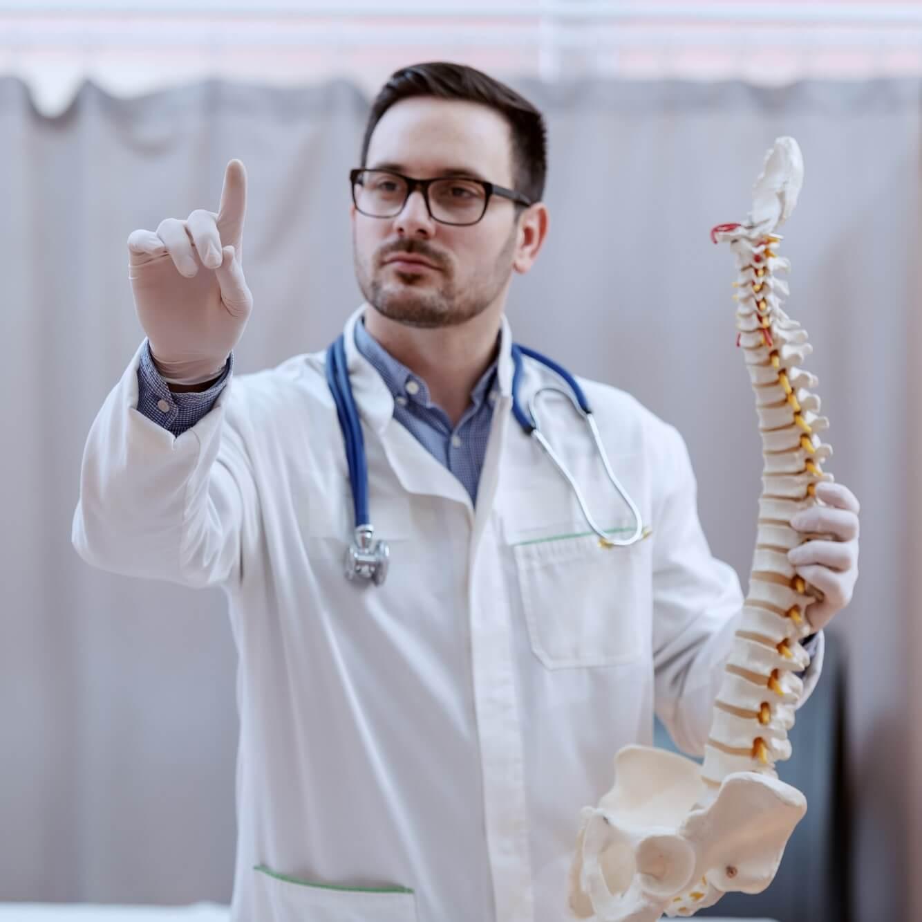 Arzt im Krankenhaus gibt Unterricht mithilfe eines Wirbelsäulenmodells