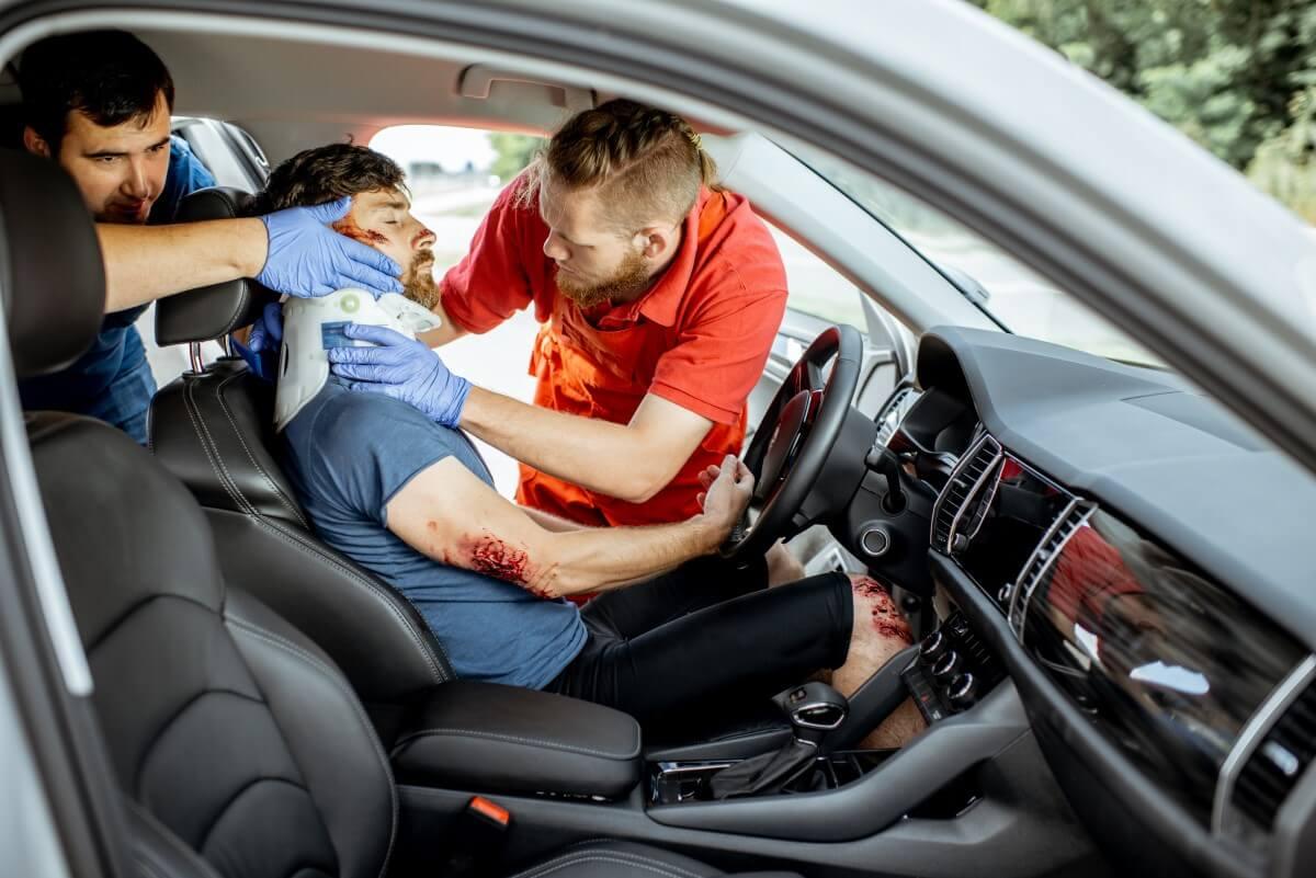Sanitäter helfen Mann nach Autounfall, vor dem Einsatz haben sie mit einer Wundsimulation geübt