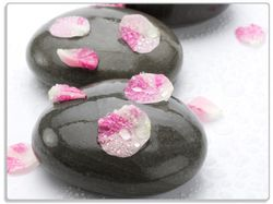 Glasunterlage Dunkle Steine mit Blütenblättern – Bild 1