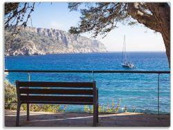 Glasunterlage Einsame Bank am Meer - Spanien im Sommer – Bild 1
