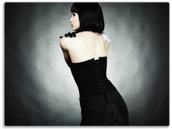 Glasunterlage Schöne Frau im schwarzen Kleid zeigt ihren Rücken – Bild 1