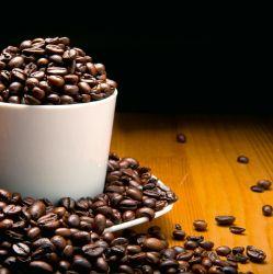 Glasbild Tasse voller Kaffeebohnen