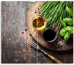 Herdabdeckplatte Kräuter (Basilikum, Schnittlauch), Öle und Gewürze auf Holzbrett in der Küche – Bild 1