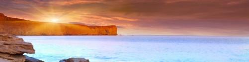 Küchenrückwand Sonnenaufgang am Meer mit Landzunge und Felsen im Wasser