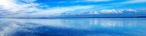 Küchenrückwand Blaue Meeresbucht in Italien mit Spiegelung im Wasser