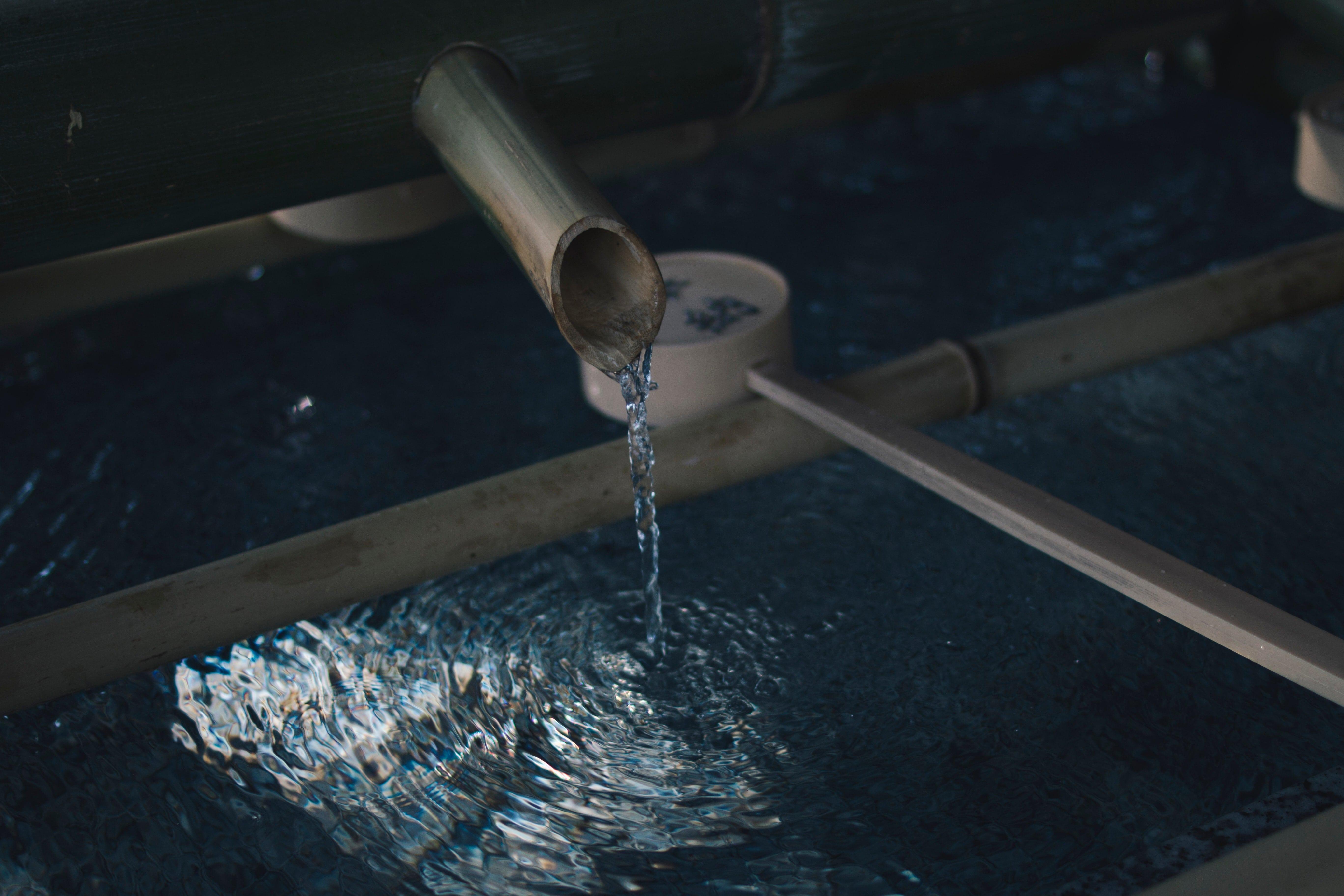 Wasser läuft durch ein Rohr in ein Becken