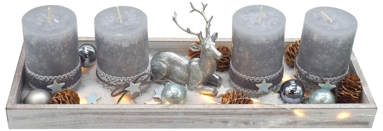 Längliches Adventsgesteck auf Holztablett dekoriert mit grauen Kerzen, Streudeko, Hirsch, Kugeln und Licherkette