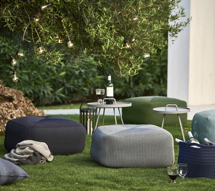 Ein Garten mit Sitzmöglichkeiten, Kissen und Tischen, auf dem Wein steht.