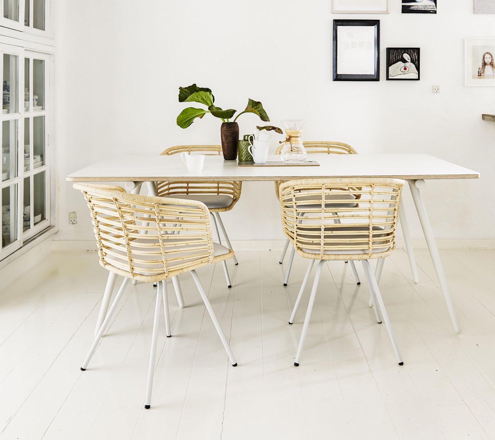 Ein Esszimmer mit einem Cane-line Esstisch und Esszimmerstühlen.