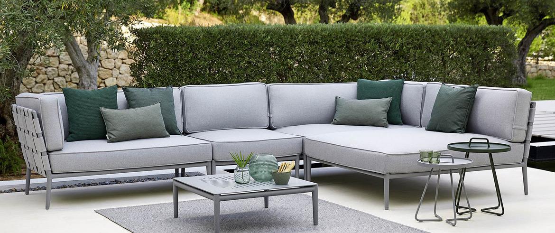 Eine Cane-line Outdoor-Lounge mit Kissen und einem Tisch auf einer Terrasse.