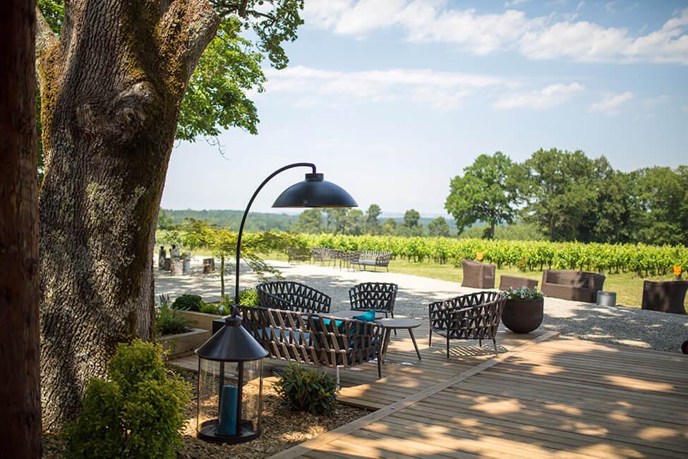 Eine Terrasse mit Stühlen und Tischen einer Gastronomie im Grünen.