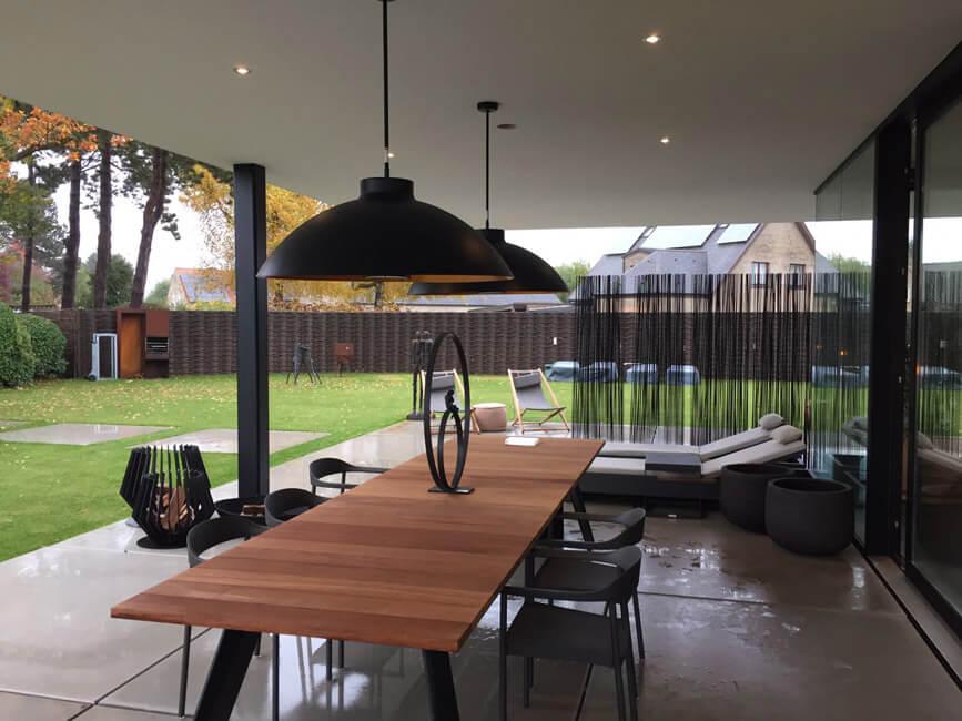 Eine Terrasse mit Gartenmöbeln und Heizstrahlern an der Decke