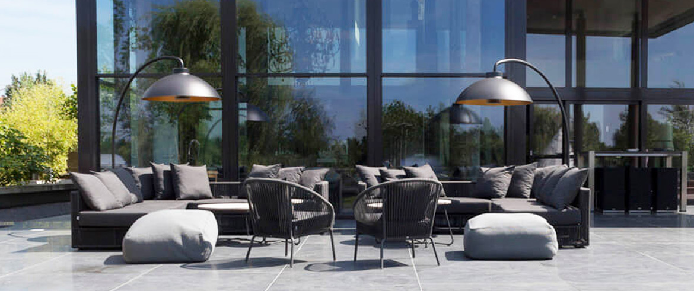 Eine Terrasse gestaltet mit einer Sitzecke mit Kissen einem Tisch und Heizstrahlern.