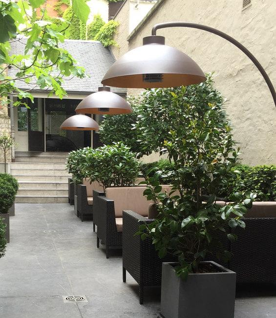 Eine Terrasse einer Gastronomie mit Stühlen, Tischen Pflanzen und Heizstrahlern
