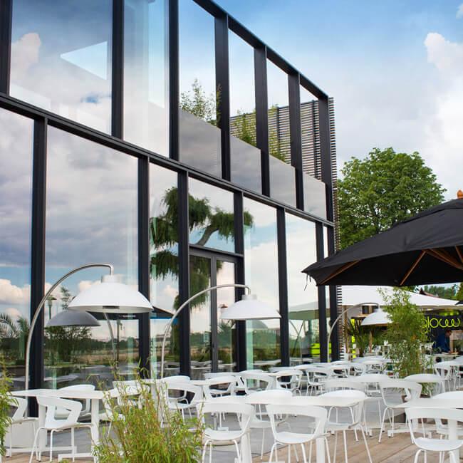 Eine Terrasse einer Gastronomie mit Stühlen, Tischen, Pflanzen und Heizstrahlern