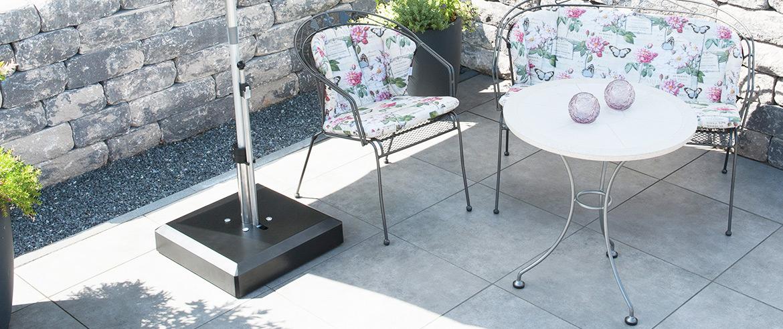 Ein schwarzer quadratischer Sonnenschirmständer aus Kunststoff auf einer Terrasse